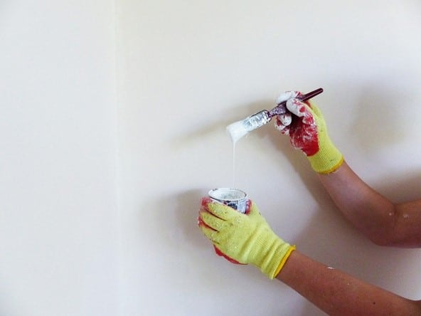 gloved hands holding paintbrush dripping white paint into can