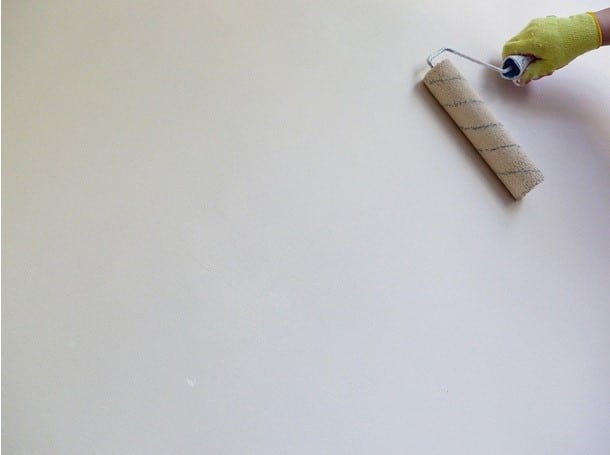 paint roller on white wall with gloved hand
