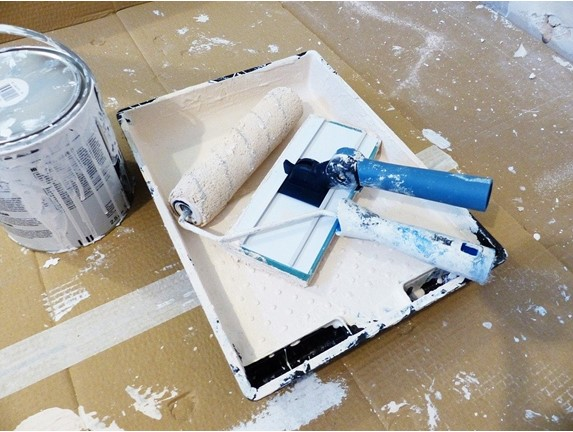 paint tray with roller on cardboard with paint can and white paint